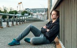 Ο νεαρός άνδρας κάθεται κοντά στην περίφραξη Στοκ εικόνα με δικαίωμα ελεύθερης χρήσης