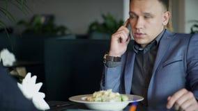 Ο νεαρός άνδρας κάθεται μέσα στο εστιατόριο και μιλά στο τηλέφωνο απόθεμα βίντεο