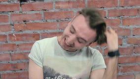 Ο νεαρός άνδρας κάθεται μελαγχολικά και γελά έξω δυνατός τοίχος εικόνας τούβλου ανασκόπησης rastre ακρόασης απόθεμα βίντεο