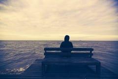 Ο νεαρός άνδρας κάθεται σε μια ξύλινη καρέκλα στη θάλασσα Στοκ Εικόνα