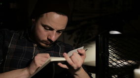Ο νεαρός άνδρας κάνει ένα σκίτσο σε ένα σημειωματάριο τη νύχτα σε έναν φραγμό απόθεμα βίντεο