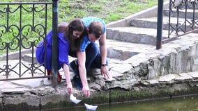 Ο νεαρός άνδρας και η γυναίκα είναι προωθημένες βάρκες εγγράφου στο πάρκο απόθεμα βίντεο