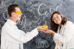 Ο νεαρός άνδρας και η γυναίκα σε ένα εργαστήριο χημείας δημιούργησαν ένα ελιξίριο στοκ εικόνες