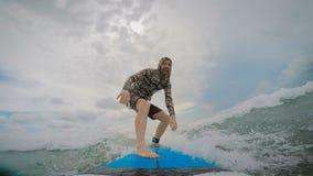 Ο νεαρός άνδρας κωπηλατεί τα χέρια του στην ιστιοσανίδα και σηκώνεται έπειτα και γύροι στο κύμα στον ωκεανό Τουρίστας ενεργά απόθεμα βίντεο