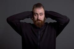 Ο νεαρός άνδρας με μια γενειάδα καλύπτει τα αυτιά του στοκ φωτογραφίες