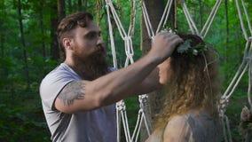 Ο νεαρός άνδρας με μια γενειάδα με μια φίλη του κοντά στην αψίδα λουλουδιών στο δάσος απόθεμα βίντεο