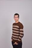 Ο νεαρός άνδρας με τα γυαλιά στην καφετιά τοποθέτηση πουλόβερ με δικούς του παραδίδει Στοκ φωτογραφία με δικαίωμα ελεύθερης χρήσης