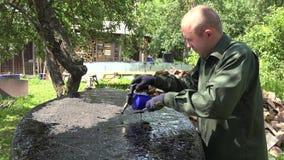 Ο νεαρός άνδρας με τον καυστήρα αερίου και η καυτή πίσσα επισκευάζουν το κατώτατο σημείο βαρκών του στον κήπο 4K φιλμ μικρού μήκους