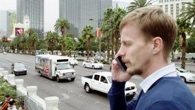 Ο νεαρός άνδρας μιλά πέρα από το smartphone του στο Λας Βέγκας απόθεμα βίντεο