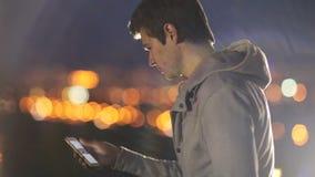Ο νεαρός άνδρας μιλά στα κοινωνικά δίκτυα στο υπόβαθρο της πόλης τη νύχτα απόθεμα βίντεο