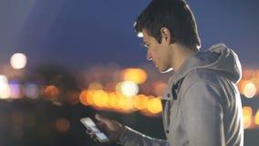 Ο νεαρός άνδρας μιλά στα κοινωνικά δίκτυα στο υπόβαθρο της πόλης τη νύχτα φιλμ μικρού μήκους