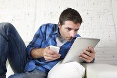 Ο νεαρός άνδρας ξαπλώνει στο σπίτι να απασχοληθεί με το κινητό τηλέφωνο και την ψηφιακή ταμπλέτα στην καταπονημένη υφιστάμενη πίε Στοκ εικόνες με δικαίωμα ελεύθερης χρήσης