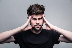 Ο νεαρός άνδρας δοκιμάζει τον έντονο πονοκέφαλο Στοκ Φωτογραφία