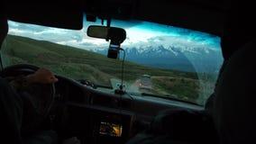 Ο νεαρός άνδρας οδηγεί ένα αυτοκίνητο στα βουνά Έννοια ταξιδιού και περιπέτειας Τονισμένη εικόνα φιλμ μικρού μήκους