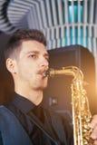 Ο νεαρός άνδρας παίζει ένα μουσικό saxophone οργάνων Στοκ εικόνες με δικαίωμα ελεύθερης χρήσης