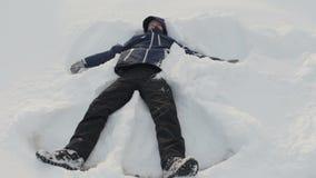 Ο νεαρός άνδρας παίζει στο χιόνι κάτω από τον ήλιο, κάνοντας τον άγγελο χιονιού, που έχει τη διασκέδαση, χαμόγελο Χειμερινές διακ απόθεμα βίντεο
