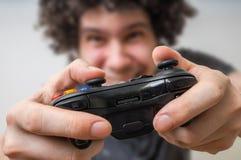 Ο νεαρός άνδρας παίζει τα τηλεοπτικά παιχνίδια και κρατά το πηδάλιο ή τον ελεγκτή Στοκ Εικόνες
