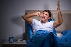Ο νεαρός άνδρας που αγωνίζεται από το θόρυβο στο κρεβάτι Στοκ Εικόνα