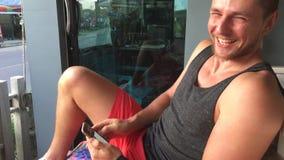 Ο νεαρός άνδρας που εξετάζει το τηλέφωνο κυττάρων, διάβασε τα σχόλια, χαμογελά και γελά απόθεμα βίντεο