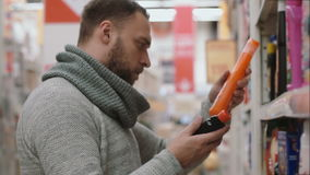 Ο νεαρός άνδρας που επιλέγει το στοιχείο στα ράφια στο κατάστημα, θέλει να αγοράσει τις οικιακές χημικές ουσίες 4K απόθεμα βίντεο