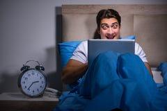 Ο νεαρός άνδρας που εργάζεται στο lap-top στο κρεβάτι Στοκ Εικόνα