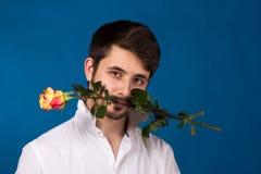Ο νεαρός άνδρας που κρατά ένα κόκκινο αυξήθηκε στο στόμα του Στοκ φωτογραφία με δικαίωμα ελεύθερης χρήσης