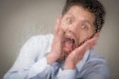 Ο νεαρός άνδρας που κραυγάζει χρησιμοποιώντας και τους δύο του παραδίδει το πρόσωπό του, πίσω από ένα θολωμένο παράθυρο με τις πτ Στοκ φωτογραφίες με δικαίωμα ελεύθερης χρήσης