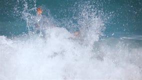 Ο νεαρός άνδρας που στέκεται στη θάλασσα από το μέση-μέγιστο σημείο δίνει το μεγάλο αντίχειρα χτυπώντας επάνω κάτω από το κύμα απόθεμα βίντεο