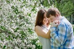 Ο νεαρός άνδρας που φιλά μιας γυναίκας παραδίδει τον ανθίζοντας κήπο άνοιξη Στοκ Εικόνες