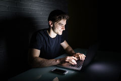 Ο νεαρός άνδρας που χρησιμοποιεί το lap-top για να μείνει όλη τη νύχτα στα κοινωνικά nerworks παρουσιάζει στο σπίτι Στοκ Φωτογραφίες