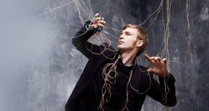 Ο νεαρός άνδρας προσπαθεί να κόψει τα λουριά με το ψαλίδι Η έννοια της απελευθέρωσης από το χειρισμό στοκ εικόνες με δικαίωμα ελεύθερης χρήσης