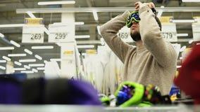 Ο νεαρός άνδρας προσπαθεί στα γυαλιά σνόουμπορντ στην υπεραγορά απόθεμα βίντεο