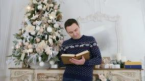 Ο νεαρός άνδρας πλέκει μέσα το πουλόβερ με τα deers διαβάζοντας ένα βιβλίο δίπλα στο χριστουγεννιάτικο δέντρο απόθεμα βίντεο