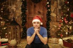 Ο νεαρός άνδρας σε Άγιο Βασίλη ΚΑΠ κάθεται στο σπίτι στα βήματα του διακοσμημένου ύφους Χριστουγέννων Στοκ Φωτογραφίες