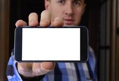Ο νεαρός άνδρας σε ένα ελεγμένο μπλε πουκάμισο κρατά ένα τηλέφωνο με Στοκ εικόνα με δικαίωμα ελεύθερης χρήσης