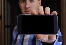 Ο νεαρός άνδρας σε ένα ελεγμένο μπλε πουκάμισο κρατά ένα τηλέφωνο με Στοκ φωτογραφίες με δικαίωμα ελεύθερης χρήσης