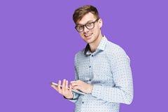 Ο νεαρός άνδρας σε ένα πουκάμισο που λειτουργεί στο lap-top στην πασχαλιά backgroundin Στοκ εικόνες με δικαίωμα ελεύθερης χρήσης