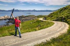 Ο νεαρός άνδρας στέκεται στο δρόμο επαρχίας, Νορβηγία Στοκ Εικόνες
