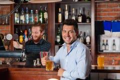 Ο νεαρός άνδρας στα γυαλιά λαβής φραγμών κάθεται στο μετρητή, πίνοντας την μπύρα Στοκ Εικόνες