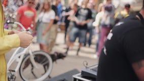 Ο νεαρός άνδρας στα γυαλιά ηλίου, κίτρινο σακάκι έρχεται στον οικοδεσπότη με το μικρόφωνο του δίνει την κάρτα Καλοκαίρι lottery απόθεμα βίντεο
