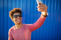 Ο νεαρός άνδρας στα περιστασιακά ενδύματα κάνει selfie πέρα από τον μπλε τοίχο Στοκ εικόνες με δικαίωμα ελεύθερης χρήσης