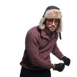 Ο νεαρός άνδρας στα χειμερινά ενδύματα και το καπέλο γουνών χορεύει Στοκ Εικόνα