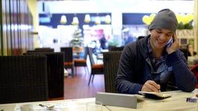 Ο νεαρός άνδρας στην κατασκευή καφέδων σημειώνει μιλώντας επάνω απόθεμα βίντεο