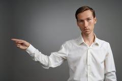 Ο νεαρός άνδρας στο άσπρο πουκάμισο δείχνει σε κάτι, που στέκεται στο γκρίζο υπόβαθρο Στοκ Φωτογραφία