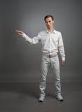 Ο νεαρός άνδρας στο άσπρο πουκάμισο δείχνει σε κάτι, που στέκεται στο γκρίζο υπόβαθρο Στοκ φωτογραφία με δικαίωμα ελεύθερης χρήσης