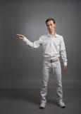 Ο νεαρός άνδρας στο άσπρο πουκάμισο δείχνει σε κάτι, που στέκεται στο γκρίζο υπόβαθρο Στοκ Εικόνα