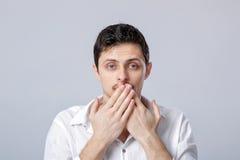 Ο νεαρός άνδρας στο άσπρο πουκάμισο καλύπτει το στόμα του με τα χέρια του σε γκρίζο Στοκ Εικόνες