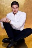 Ο νεαρός άνδρας στο άσπρο πουκάμισο κόβει το χρυσό ρολόι Στοκ Εικόνα
