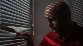 Ο νεαρός άνδρας στο γραφείο κοιτάζει μέσω των τυφλών απόθεμα βίντεο