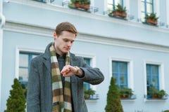Ο νεαρός άνδρας στο παλτό εξετάζει το ρολόι του στεμένος υπαίθρια στην πόλη Έννοια χρονικού διορισμού στοκ φωτογραφία